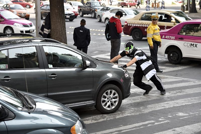 The mighty Peatonito (Little Pedestrian) pushes cars blocking the path of pedestrians, creates crosswalks with spray paint, and climbs on vehicles parked on sidewalks -- though his mother has begged him to stop stepping on them (AFP Photo/Yuri Cortez)