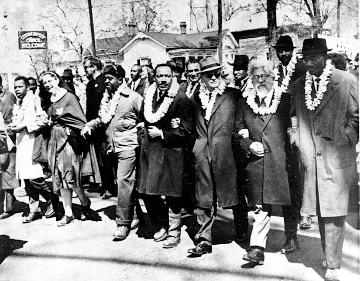 Dr. Martin Luther King Jr. links arms with other civil rights leaders as they begin the march to the state capitol in Montgomery from Selma, Ala. on March 21, 1965. The demonstrators are marching for voter registration rights for blacks. Accompanying Dr. Martin Luther King Jr. (fourth from right), are on his left Ralph Bunche, undersecretary of the United Nations, Rabbi Abraham Joshua Heschel, and Rev. Fred Shuttlesworth. They are wearing leis given by a Hawaiian group.