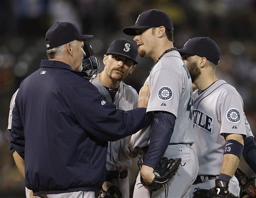 Seattle Mariners' Blake Beavan, second from right, listens to pitching coach Carl Willis during the fifth inning of a baseball game against the against the Oakland Athletics on Friday, Sept. 28, 2012, in Oakland, Calif. (AP Photo/Ben Margot)
