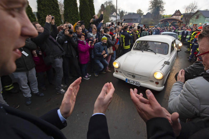 People welcome the legendary GDR cars Trabant (Trabi), during a symbolic wall opening, celebrating the 30th anniversary of the falling wall in the outdoor area of the German-German museum in Moedlareuth, Germany, Saturday, Nov. 9, 2019. Moedlareuth, named 'Little Berlin', was the symbol of a divided village along the borderline between East and West Germany. The border ran straight through the little village. (AP Photo/Jens Meyer)