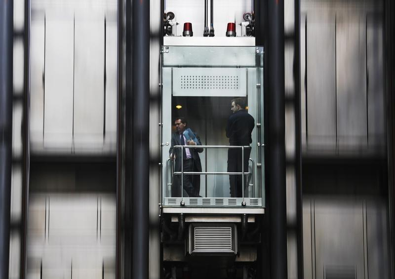 People travel in a lift at the Lloyds of London building in the financial district of the City of London January 29, 2013. REUTERS/Luke Macgregor