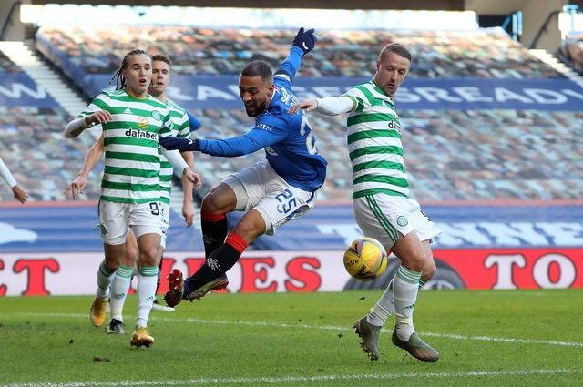 Kemar Roofe, centre, goes down under the challenge of Leigh Griffiths, right