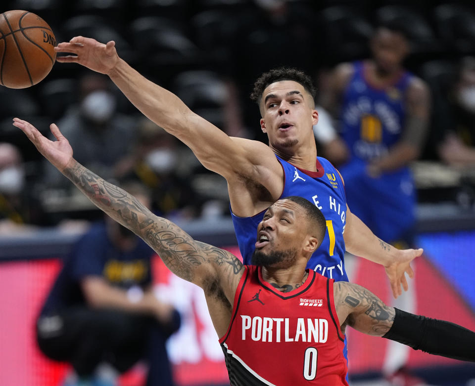Portland Trail Blazers guard Damian Lillard (0) goes up for a shot against Denver Nuggets forward Michael Porter Jr. (1) in the second half of Game 1 of a first-round NBA basketball playoff series Saturday, May 22, 2021, in Denver. (AP Photo/Jack Dempsey)