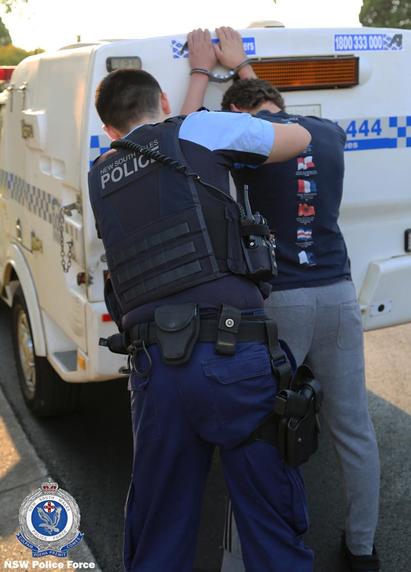 Police hold alleged terrorist Youssef Uweinat against a car after arrest from Riverwood home in Sydney.