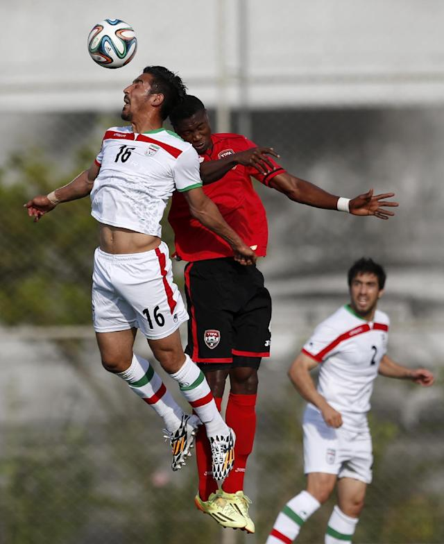 Iran's Reza Ghouchannejad, left, and Trinidad's Sheldon Bateau go up for the ball during the first half of an international soccer friendly at the Corinthians soccer team training center Sao Paulo, Brazil, on Sunday, June 8, 2014. Iran will play in group F of the 2014 soccer World Cup. (AP Photo/Julio Cortez)