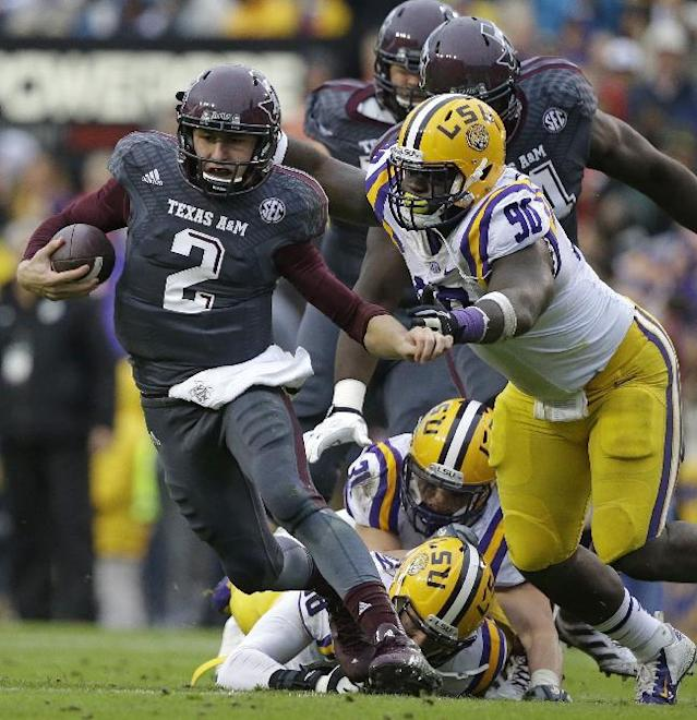 FILE - In this Nov. 23, 2013 file photo, Texas A&M quarterback Johnny Manziel (2) scrambles to avoid a tackle by LSU defensive tackle Anthony Johnson (90) in the first half of an NCAA college football game in Baton Rouge, La. Manziel is again a finalist for the Heisman Trophy, with a chance to become just the second player to win the award twice. (AP Photo/Gerald Herbert, File)