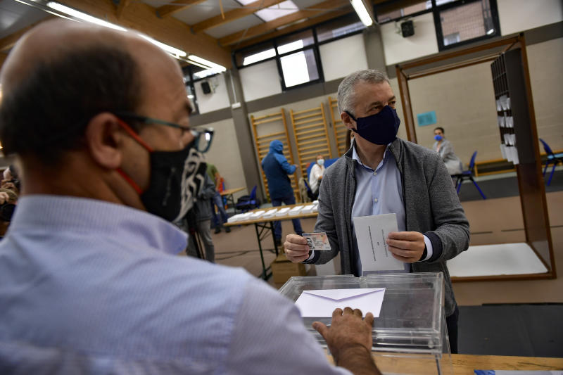 Inigo Urkullo, Basque Lehendakari or Regional President, right, wears a face mask as protection against the coronavirus while voting in a polling station during Basque regional election in the village of Durango, northern Spain, Sunday, July 12, 2020. (AP Photo/Alvaro Barrientos)