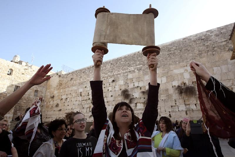"""A member of the liberal Jewish religious group Women of the Wall wears a """"Tallit"""", a Jewish prayer shawl traditionally worn by men, as she holds up a Torah scroll at the Western Wall on March 11, 2016 (AFP Photo/)"""