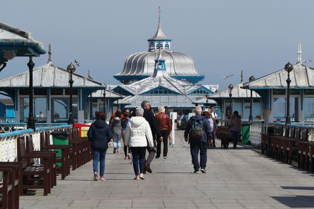 People walk along the pier in Llandudno, Wales, where lockdown restrictions have eased