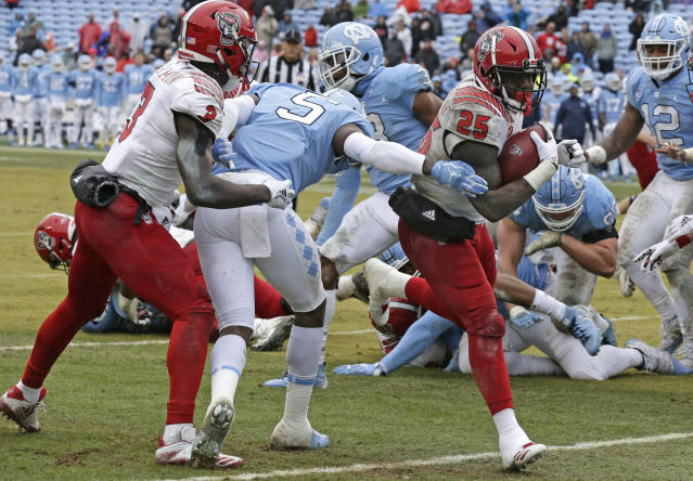 "North Carolina State's <a class=""link rapid-noclick-resp"" href=""/ncaaf/players/251290/"" data-ylk=""slk:Reggie Gallaspy"">Reggie Gallaspy</a> II (25) scores a touchdown as <a class=""link rapid-noclick-resp"" href=""/ncaaf/players/266489/"" data-ylk=""slk:Kelvin Harmon"">Kelvin Harmon</a> (3) blocks North Carolina's <a class=""link rapid-noclick-resp"" href=""/ncaaf/players/263528/"" data-ylk=""slk:Patrice Rene"">Patrice Rene</a> (5) during the second half Saturday. (AP Photo/Gerry Broome)"
