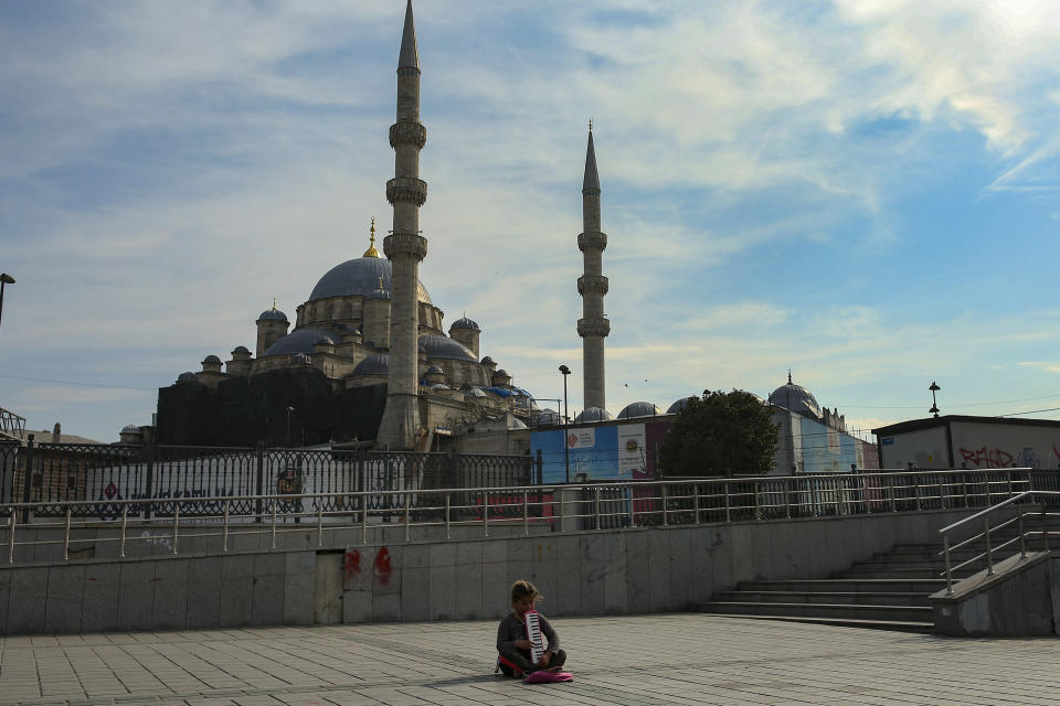 A child plays music for money backdropped by the Yeni Cami (New Mosque) in Istanbul, Saturday, April 3, 2021. The streets of Istanbul, reflect a weekend curfew resumed as the number of COVID-19 cases hit record levels, and with renewed restrictions announced for the Islamic month of Ramadan which begins on April 13. (AP Photo/Emrah Gurel)