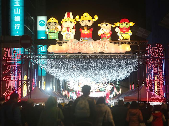 People in Taiwan wear protective face masks and gather to view lanterns on display for the Chinese lunar new year,
