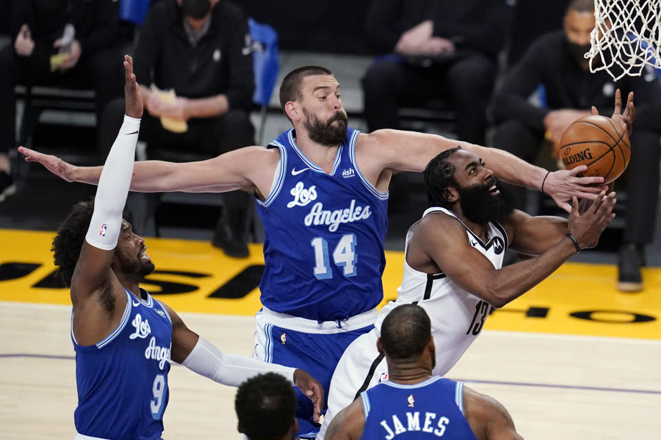 Brooklyn Nets guard James Harden, right, drives to the basket as Los Angeles Lakers center Marc Gasol (14) defends during the first half of an NBA basketball game Thursday, Feb. 18, 2021, in Los Angeles. (AP Photo/Marcio Jose Sanchez)