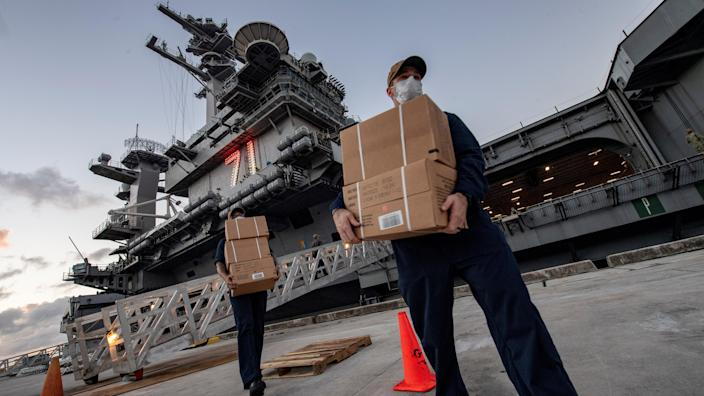 Sailors assigned to the aircraft carrier Theodore Roosevelt carry food supply boxes for sailors who tested negative for the coronavirus and are asymptomatic. (U.S. Navy/MC1 Julio Rivera/Anadolu Agency via Getty Images)