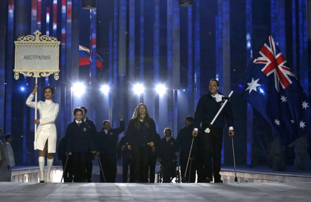 Australia's flag-bearer Cameron Rahles-Rahbula (R), leads his country's contingent during the opening ceremony of the 2014 Paralympic Winter Games in Sochi, March 7, 2014. REUTERS/Alexander Demianchuk (RUSSIA - Tags: OLYMPICS SPORT)