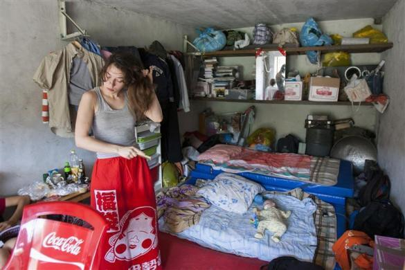 Political activist Natalia Sokol brushes her hair as Gera, the baby of fellow activist Nadezhda Tolokonnikova, lies on a mattress in the car shed that serves as home for the Voina activist group in Moscow, July 15, 2008. Tolokonnikova later became a member of Pussy Riot.
