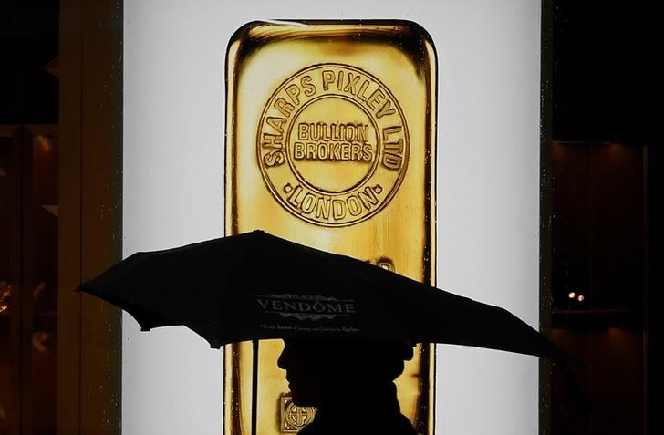 A pedestrian walks past a window displaying a representation of a gold bar at a bullion broker in Piccadilly, London, Britain