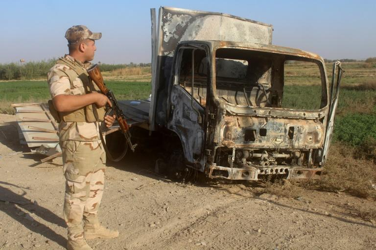 An Iraqi soldier inspects a burnt-out vehicle as troops gather on November 11, 2017, in readiness for an assault on the town of Rawa, the last in the country still held by the Islamic State group