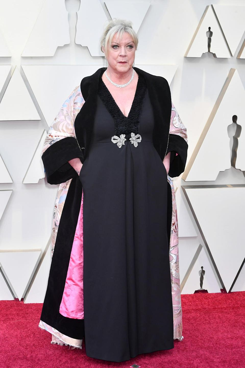 <p>Wearing a black embellished gown with a silk printed robe.</p>