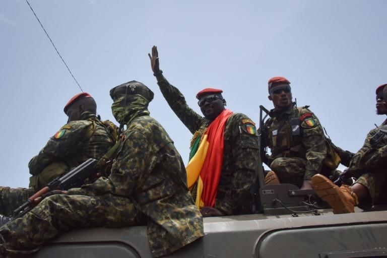 Coup leader Lieutenant Colonel Mamady Doumbouya, centre, waving to the crowd as he arrived at parliament on Monday for a meeting with outgoing ministers (AFP/CELLOU BINANI)