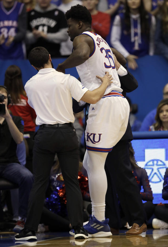 Kansas center Udoka Azubuike (35) is aided by training staff after an injury during the first half of an NCAA college basketball game against Wofford in Lawrence, Kan., Tuesday, Dec. 4, 2018. (AP Photo/Orlin Wagner)