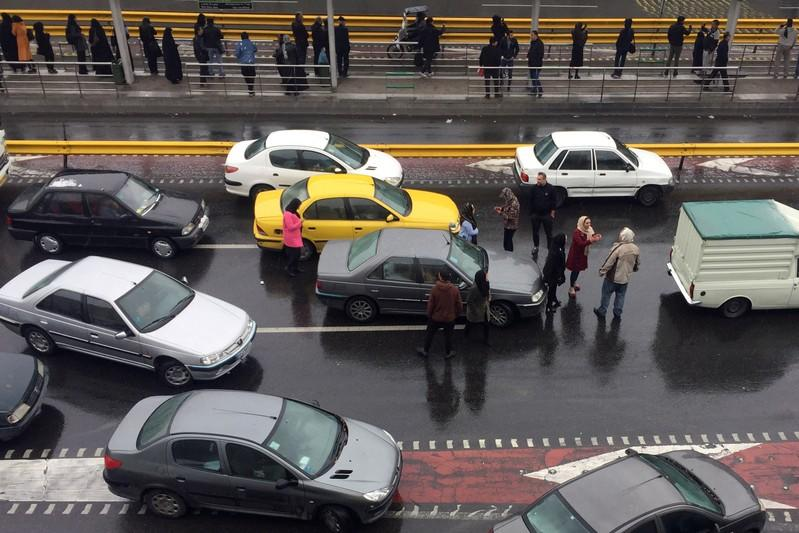 People stop their cars in a highway to show their protest against increased gas price in Tehran