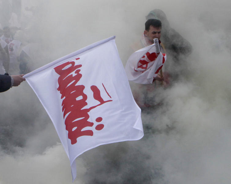 Workers with Solidarity trade union flags and throwing smoke grenades are protesting a government plan to raise retirement age to 67 outside the in Parliament, in Warsaw, Poland on Friday, March 30, 2012. Prime Minister Donald Tusk says it is necessary to raise the current retirement age of 60 for women and 65 for men in order to cut state budget deficit. (AP Photo/Czarek Sokolowski)