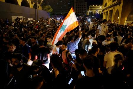 A demonstrator holds a Lebanese flag during a protest over deteriorating economic situation in Beirut