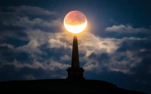 The partial lunar eclipse is visible above Stoodley Pike near Todmorden in West Yorkshire - Credit:  Danny Lawson/ PA