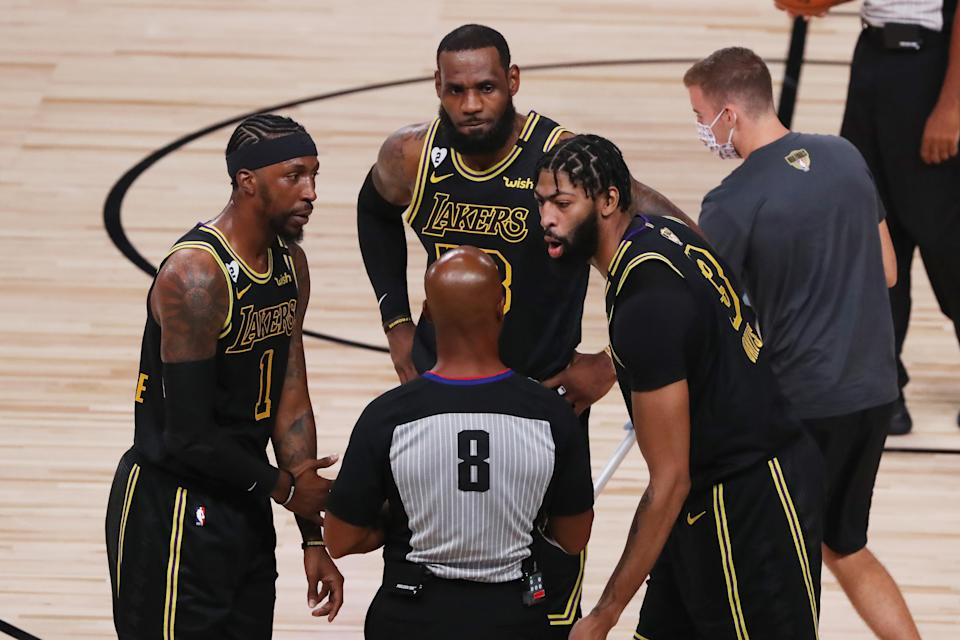 LAKE BUENA VISTA, FLORIDA - OCTOBER 09: LeBron James #23 of the Los Angeles Lakers, Kentavious Caldwell-Pope #1 of the Los Angeles Lakers and Anthony Davis #3 of the Los Angeles Lakers talk with referee Marc Davis #8 during the first quarter against the Miami Heat in Game Five of the 2020 NBA Finals at AdventHealth Arena at the ESPN Wide World Of Sports Complex on October 9, 2020 in Lake Buena Vista, Florida. NOTE TO USER: User expressly acknowledges and agrees that, by downloading and or using this photograph, User is consenting to the terms and conditions of the Getty Images License Agreement. (Photo by Sam Greenwood/Getty Images)