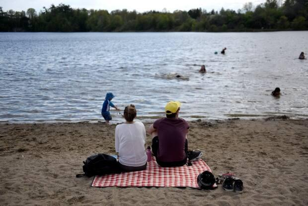 Beachgoers sit on the shore of the Rideau River at Mooney's Bay beach in Ottawa last weekend. On Saturday, the city's health officials reported 78 COVID-19 cases and two new deaths. (Justin Tang/Canadian Press - image credit)
