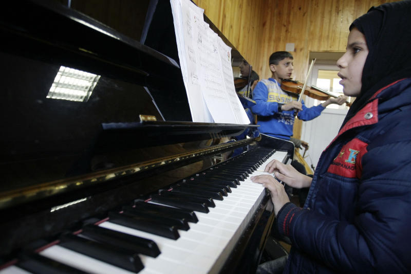 In this Monday,  Jan. 7, 2013, photo an Afghan girl, right, practices playing the piano in a class at the Afghanistan National Institute of Music in Kabul, Afghanistan. Dozens of Afghan teenagers including former street kids or orphans aged 10 to 22, will be playing in the Afghan Youth Orchestra which begins a 12-day U.S. tour on Feb. 3 and includes concerts at Washington's Kennedy Center - President Barrack Obama has been invited - New York's Carnegie Hall and the New England Conservatory in Boston. (AP Photo/Musadeq Sadeq)