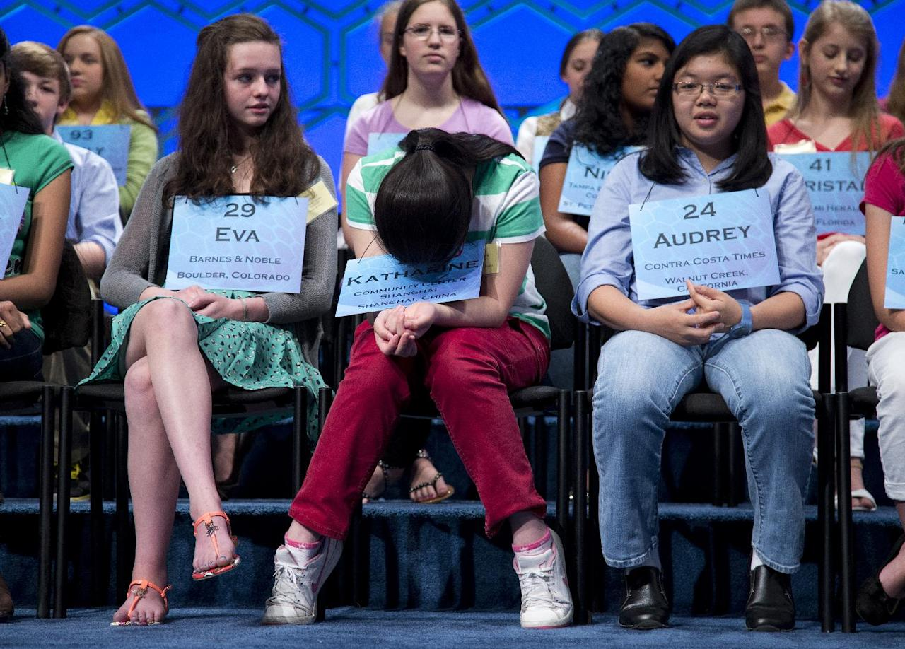 Katharine Wang, 11, of Beijing, China, center, gathers herself before the start of the semifinal round of the National Spelling Bee, Thursday, May 30, 2013, in Oxon Hill, Md. From left are, Eva Kitlen of Niwot, Colo., Wang, and Audrey Bantug, 13, of San Ramon, Calif. (AP Photo/Evan Vucci)