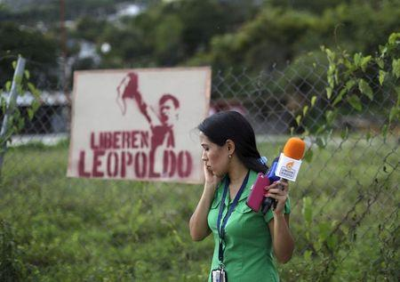 A journalist speaks on her cellphone in front of a sign with the image of jailed Venezuelan opposition leader Leopoldo Lopez outside the prison of Ramo Verde, on the outskirts of Caracas, June 18, 2015.  REUTERS/Jorge Dan Lopez