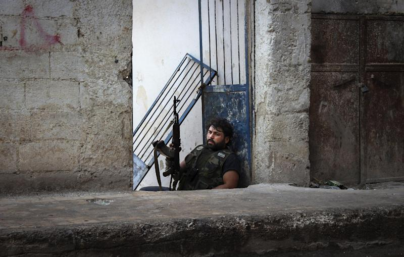 In this Tuesday, Oct. 30, 2012 photo, Mustafa, a rebel from the town of Bennish, watches for a sniper firing down a street in the town of Harem, Syria. Despite two weeks of attacking a Roman-era citadel in which pro-Assad militia are dug in, the rebels failed to secure the town. (AP Photo/Mustafa Karali)