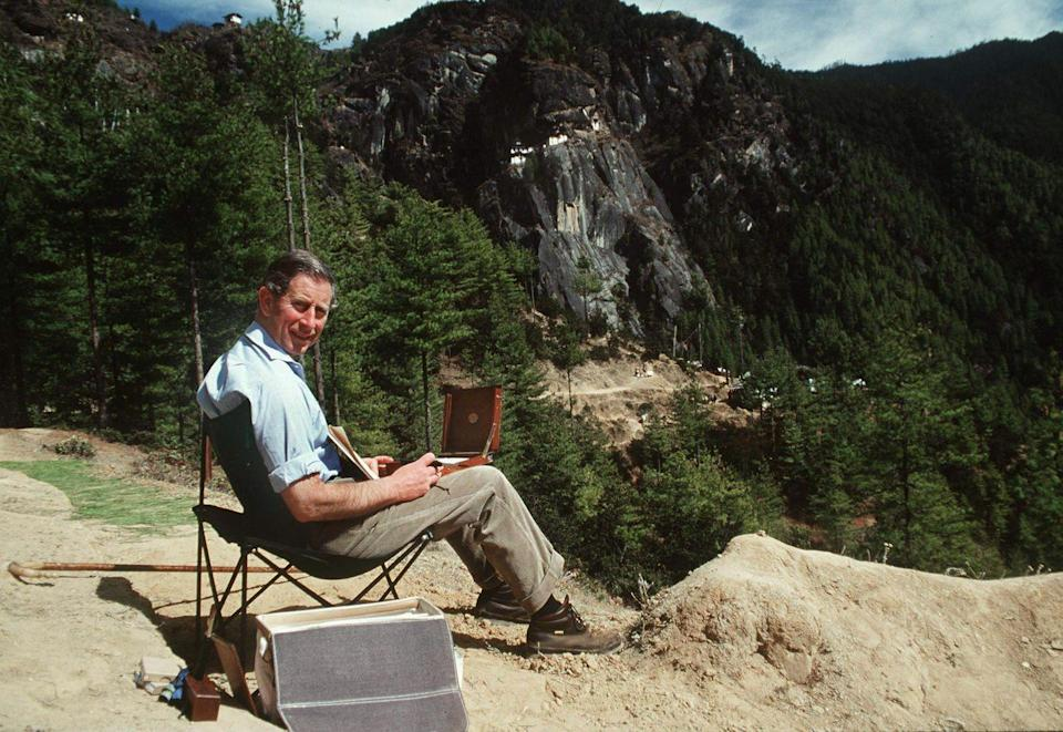 <p>Even the royals sometimes need to stop and take in the scenery. In this photo from 1998, Prince Charles stopped to paint a watercolor in the middle of his hike of the Himalayas. </p>