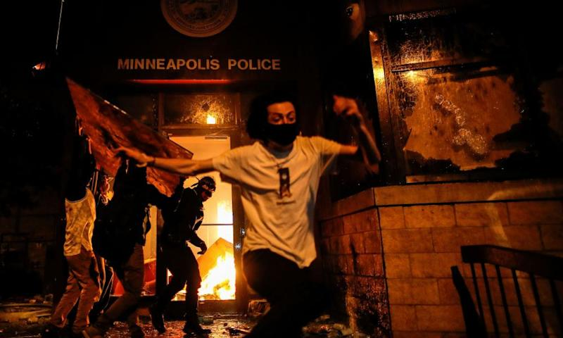 Protesters react set fire to the entrance of a police station in Minneapolis, Minnesota.