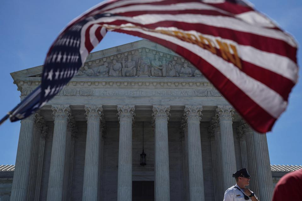 <p>A man holds a flag outside the U.S. Supreme Court, as the Trump v. Hawaii case regarding travel restrictions in the U.S. remains pending, in Washington, June 25, 2018. (Photo: Toya Sarno Jordan/Reuters) </p>
