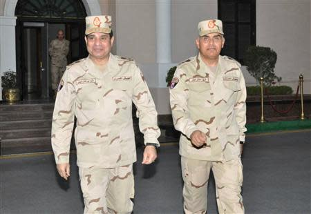 Egypt's army chief Field Marshal Abdel Fattah al-Sisi (L) walks with Gen. Sidqi Sobhi (R) after meeting with members of the Supreme Council of the Armed Forces, in Cairo March 26, 2014. REUTERS/Egyptian Ministry of Defence/Handout