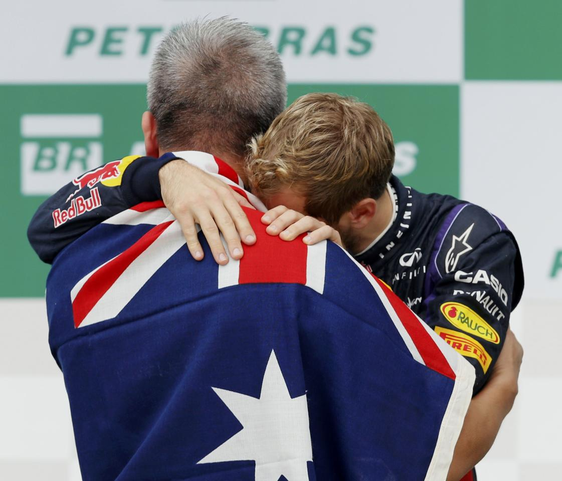 Red Bull Formula One driver Sebastian Vettel (R) of Germany embraces an emotional team Chiropractor Paul Cheung after the Brazilian F1 Grand Prix at the Interlagos circuit in Sao Paulo November 24, 2013. REUTERS/Paulo Whitaker (BRAZIL - Tags: SPORT MOTORSPORT F1)