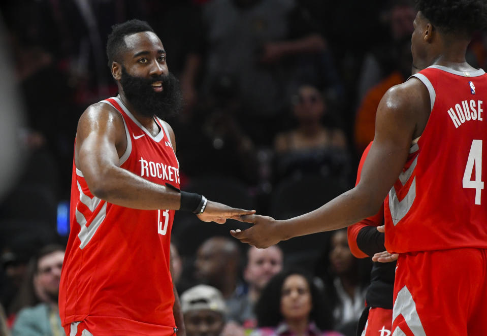 James Harden and Danuel House in red Rockets jerseys slap hands.