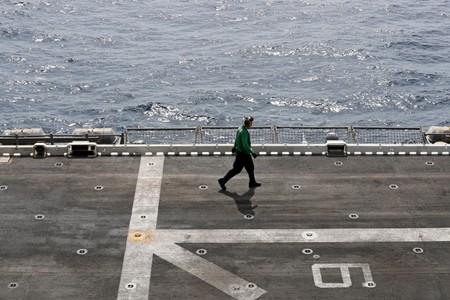 FILE PHOTO: A U.S. sailor walks on the flight deck of USS Boxer (LHD-4) in the Arabian Sea off Oman