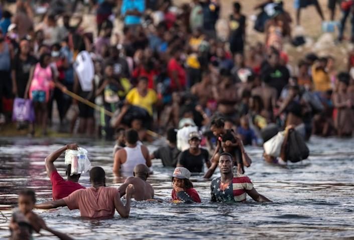 Immigrants, mostly from Haiti, gather on the banks of the Rio Grande in Ciudad Acuna, Mexico.