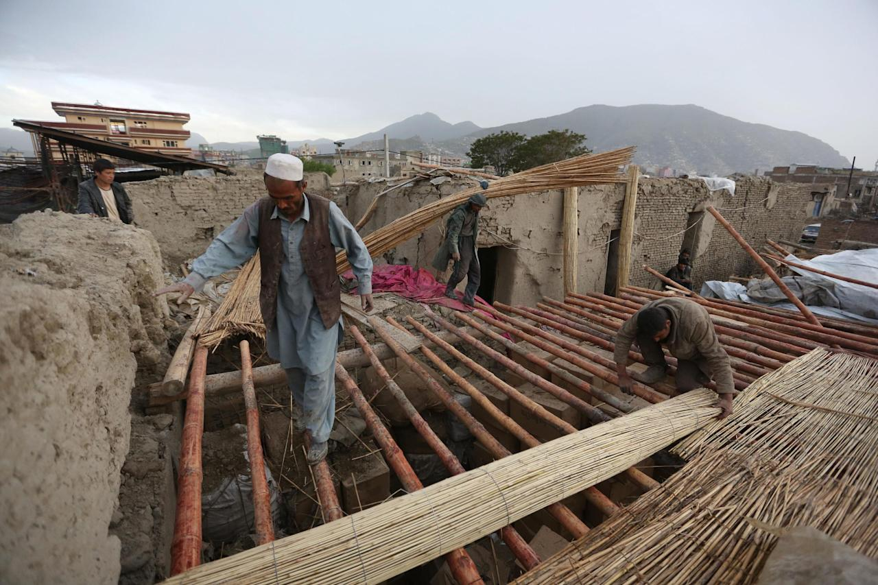 Afghan men build temporary shelter in a good's warehouse destroyed after yesterday's Taliban-claimed deadly suicide attack in Kabul, Afghanistan, Wednesday, April 20, 2016. The Afghan Interior Ministry says the death toll from Tuesday's Taliban attack in Kabul has risen sharply overnight. (AP Photo/Rahmat Gul)