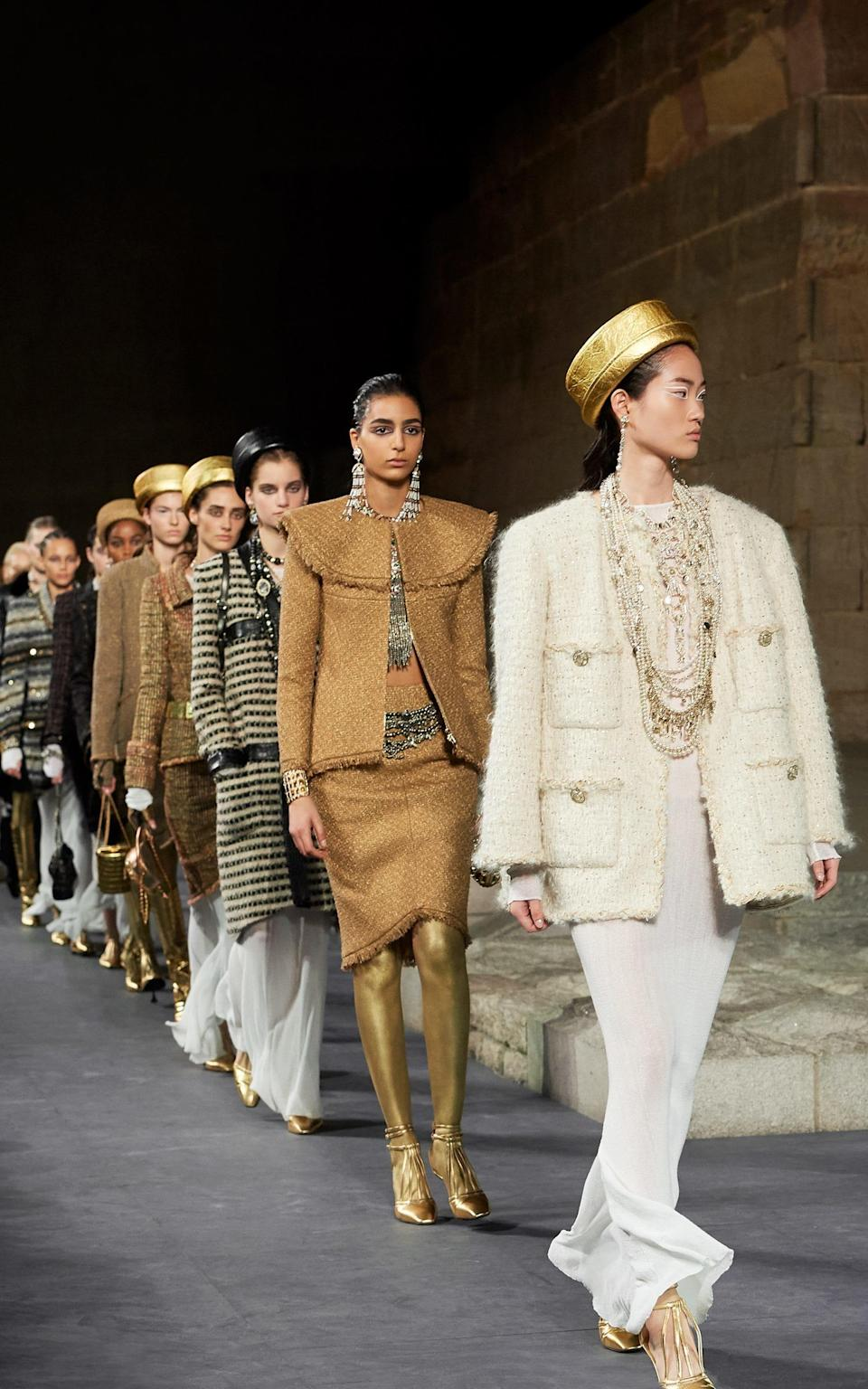 Models with legs painted gold wear embellished tweed and carry scarab-shaped iridescent bags - Chanel