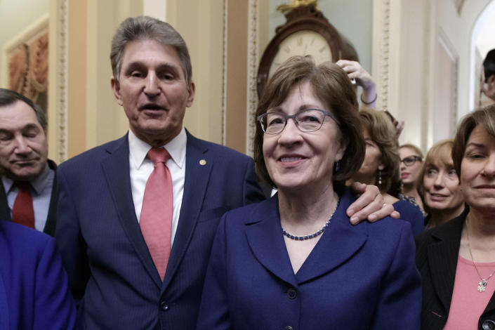 In this file photo from Monday, Jan. 22, 2018, Sen. Susan Collins, R-Maine, is joined by Sen. Joe Manchin, D-W.Va., left, and others as they celebrate the bipartisan effort to end a government shutdown, at the Capitol in Washington. Collins, a moderate Republican, is joining Manchin, a moderate Democrat, in opposition to confirming Neera Tanden, President Joe Biden's nominee for budget director. (AP Photo/J. Scott Applewhite, file)