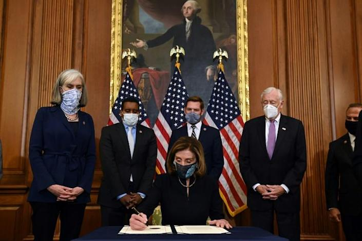 Speaker of the House Nancy Pelosi signs the article of impeachment after the US House of Representatives voted to impeach US President Donald Trump at the US Capitol