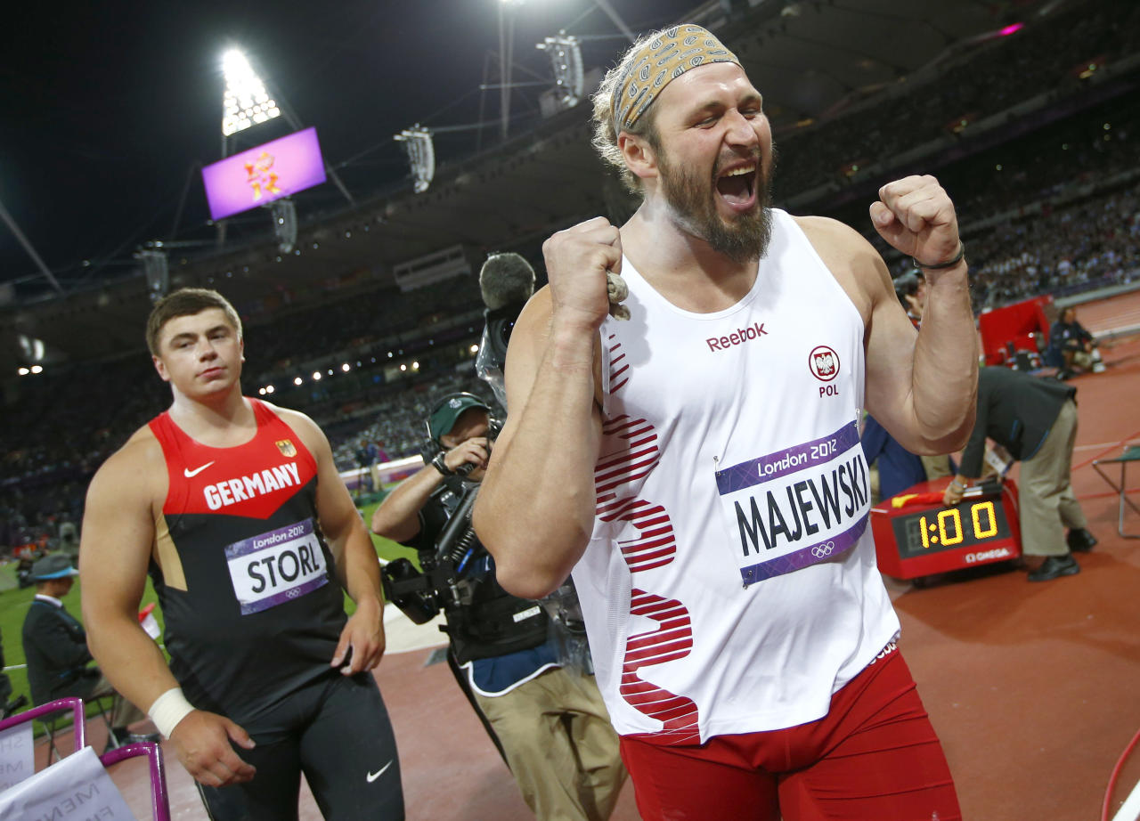 Germany's David Storl (L) watches as Poland's Tomasz Majewski celebrates after winning the men's shot put final during the London 2012 Olympic Games at the Olympic Stadium August 3, 2012. Majewski placed first ahead of Storl who placed second and Reese Hoffa of the U.S who finished third.                  REUTERS/Kai Pfaffenbach (BRITAIN  - Tags: OLYMPICS SPORT ATHLETICS)