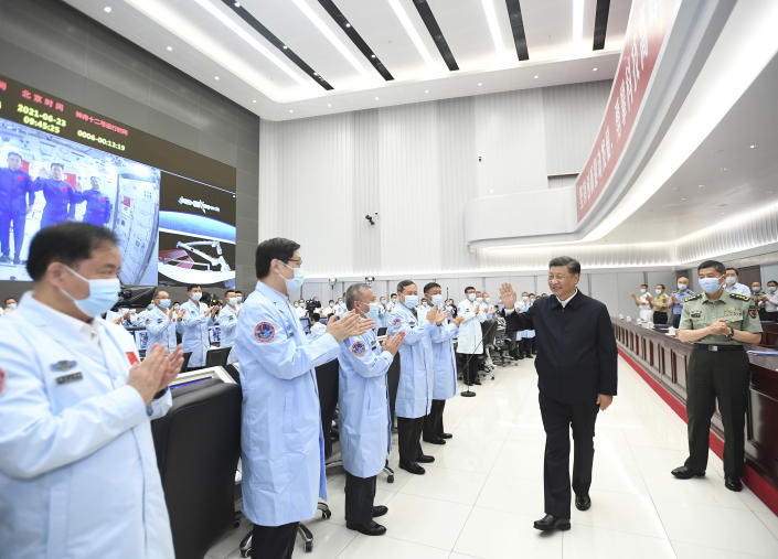 In this photo released by China's Xinhua News Agency, Chinese President Xi Jinping greets workers after having a video conversation with the three astronauts aboard China's space station core module Tianhe at the Beijing Aerospace Control Center in Beijing, Wednesday, June 23, 2021. (Yan Yan/Xinhua via AP)