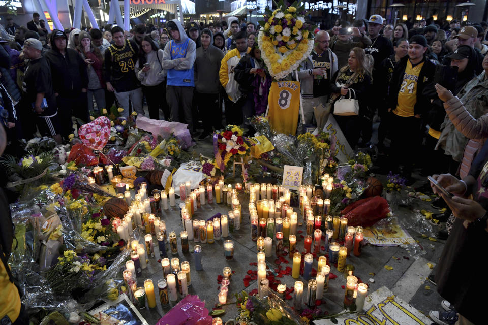 People gather at a memorial near Staples Center after the death of Laker legend Kobe Bryant Sunday, Jan. 26, 2020, in Los Angeles. (AP Photo/Michael Owen Baker)